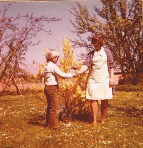 Mor Iris får vårblommor av Sven i trädgården på Näs